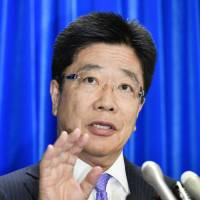 Labor minister Katsunobu Kato takes questions from reporters during a news conference at the ministry on Tuesday.   KYODO