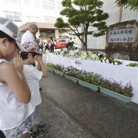People pray silently Monday in front of a monument set up at Bairin Elementary School in Asaminami Ward, Hiroshima. Monday was the fourth anniversary of landslides that killed 77 people in the city. | KYODO