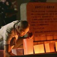 A man lights a lantern in front of a cenotaph in Hiroshima's Asaminami Ward early Monday to commemorate the fourth anniversary of landslides that killed 77 people in the city. | KYODO