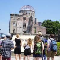 Tourists on Sunday look at the Atomic Bomb Dome in Hiroshima. The building, one of the few to survive the atomic bombing in August 1945, is one of the most popular tourist spots in the city. But several other places in the prefecture are trying to recover from damage caused by the torrential rain that triggered thousands of landslides throughout western Japan last month. | MAGDALENA OSUMI