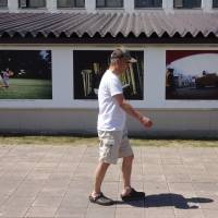 A visitor to a summer photography festival walks by a wall of photos on display in downtown Higashikawa, Hokkaido, in early August.   ERIC JOHNSTON