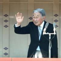 Emperor Akihito waves to the crowd gathered at the Imperial Palace in Tokyo to celebrate his 84th birthday on Dec. 23, 2017, as Crown Prince Naruhito looks on. | KYODO