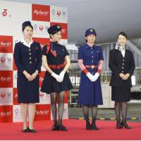Japan Airlines Co. President Yuji Akasaka (far left) poses during a news conference with flight attendants who wear past uniforms on Thursday in Ota Ward, Tokyo. | KYODO