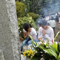 Women offer prayers Sunday to the victims of the 1985 Japan Airlines jumbo jet crash that claimed the lives of 520 people at Osutaka Ridge in Gunma Prefecture. | KYODO