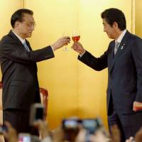 Prime Minister Shinzo Abe and Chinese Premier Li Keqiang make a toast at a welcome reception in Tokyo on May 10. | KYODO