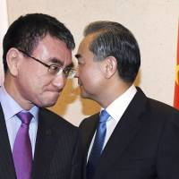 Foreign Minister Taro Kono (left) and his Chinese counterpart Wang Yi pass each other before holding talks Thursday in Singapore.   KYODO