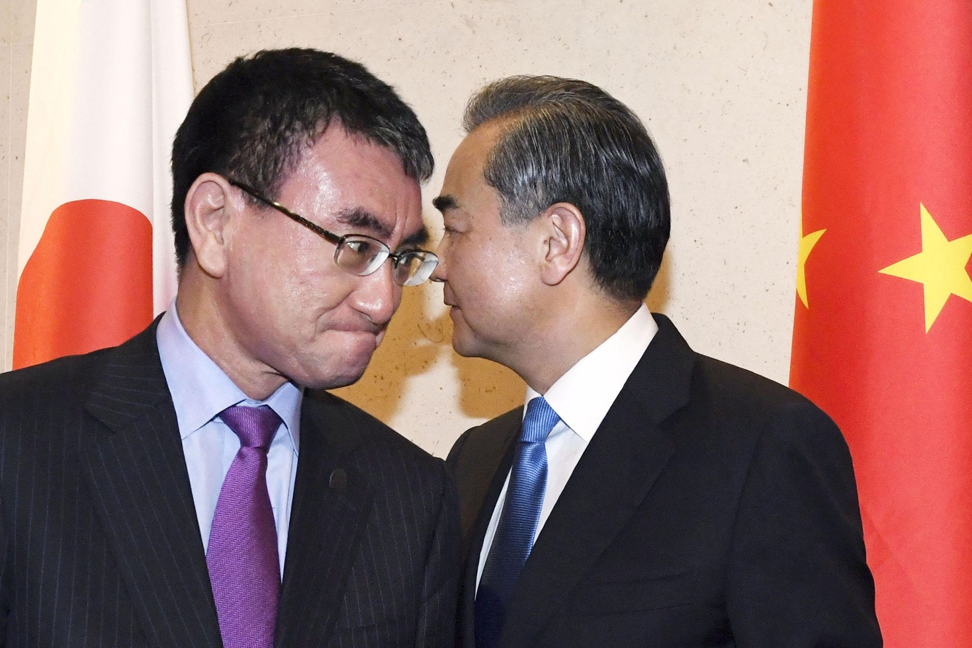 Foreign Minister Taro Kono (left) and his Chinese counterpart Wang Yi pass each other before holding talks Thursday in Singapore. | KYODO