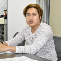 A Filipino technical intern, who filed a lawsuit against a local construction firm and the group coordinating his program, speaks at a news conference in Kumamoto in June. | KYODO