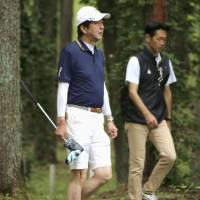 Prime Minister Shinzo Abe plays golf Tuesday while on vacation in Narusawa, Yamanashi Prefecture. Abe is expected to announce soon his intention to run for the ruling party's presidential election, set for Sept. 20. | KYODO