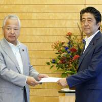 Prime Minister Shinzo Abe receives a set of proposals from Akira Amari, adviser to the Liberal Democratic Party faction led by Deputy Prime Minister Taro Aso, at the Prime Minister's Office in Tokyo on Monday. | KYODO