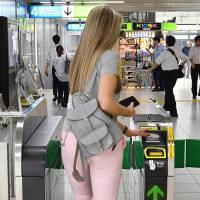 A woman extends her left arm to wave her IC card over a card reader on a standard train station ticket gate in Tokyo. | YOSHIAKI MIURA