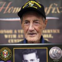 Gilbert Howland, of Langhorn, Pennsylvania, one of the few remaining members of the famed WWII Army unit Merrill's Marauders, poses for a portrait with a plaque bearing a photo of his younger self, during a gathering of remaining members, family and history buffs, in New Orleans Tuesday. | GERALD HERBERT / VIA AP