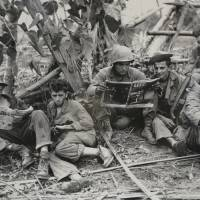 This Aug. 2, 1944 photo, courtesy of the U.S. Army Signal Corps, with a caption that reads 'Ind-Bur cpgn, Sitapur Myitkyina, Burma 2 Aug 44, 5307th. war cool Infantry time out to read old mags. Less than 75 yards from enemy positions,' shows members of the famed WWII Army unit Merrill's Marauders, on display during a gathering of remaining members, family and history buffs, in New Orleans Tuesday. | U.S. ARMY SIGNAL CORPS / VIA AP