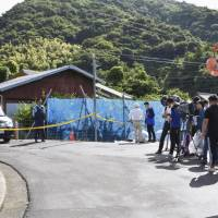 A police officer stands behind a police cordon near the site in Suo-Oshima Island, Yamaguchi Prefecture, where 2-year-old Yoshiki Fujimoto, who went missing on Sunday, was found early Wednesday morning. | KYODO