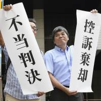 Supporters hold up banners saying 'Unfair ruling' and 'Appeal dismissed' after the Tokyo High Court on Friday upheld a life sentence handed down by the Utsunomiya District Court in 2016 for Takuya Katsumata. | KYODO