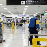 A foreign worker (left) engages in cleaning work late at night at Narita airport on Aug. 11. | KYODO