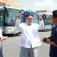 North Korean leader Kim Jong Un visits an unidentified site in the country for a trial operation of a new type of trolley bus in this photo released on Aug. 4. | AFP-JIJI