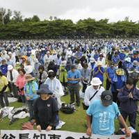 Protesters against a joint plan to relocate a U.S. military base in Okinawa observe a moment of silence Saturday for Gov. Takeshi Onaga, who died of cancer on Wednesday, at a park in Naha. | KYODO