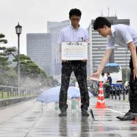 Officials test sprinklers on Tokyo street as city looks for ways to keep Olympic athletes and spectators cool