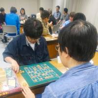 A man (front) plays shogi with a staffer at a monthly session for hikikomori in Sapporo last month. | KYODO