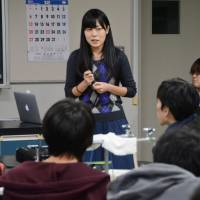 A graduate student at Tohoku University lectures students at Miyagi First Senior High School in Sendai in December 2015 as part of the university's efforts to encourage young people to study science. | KYODO