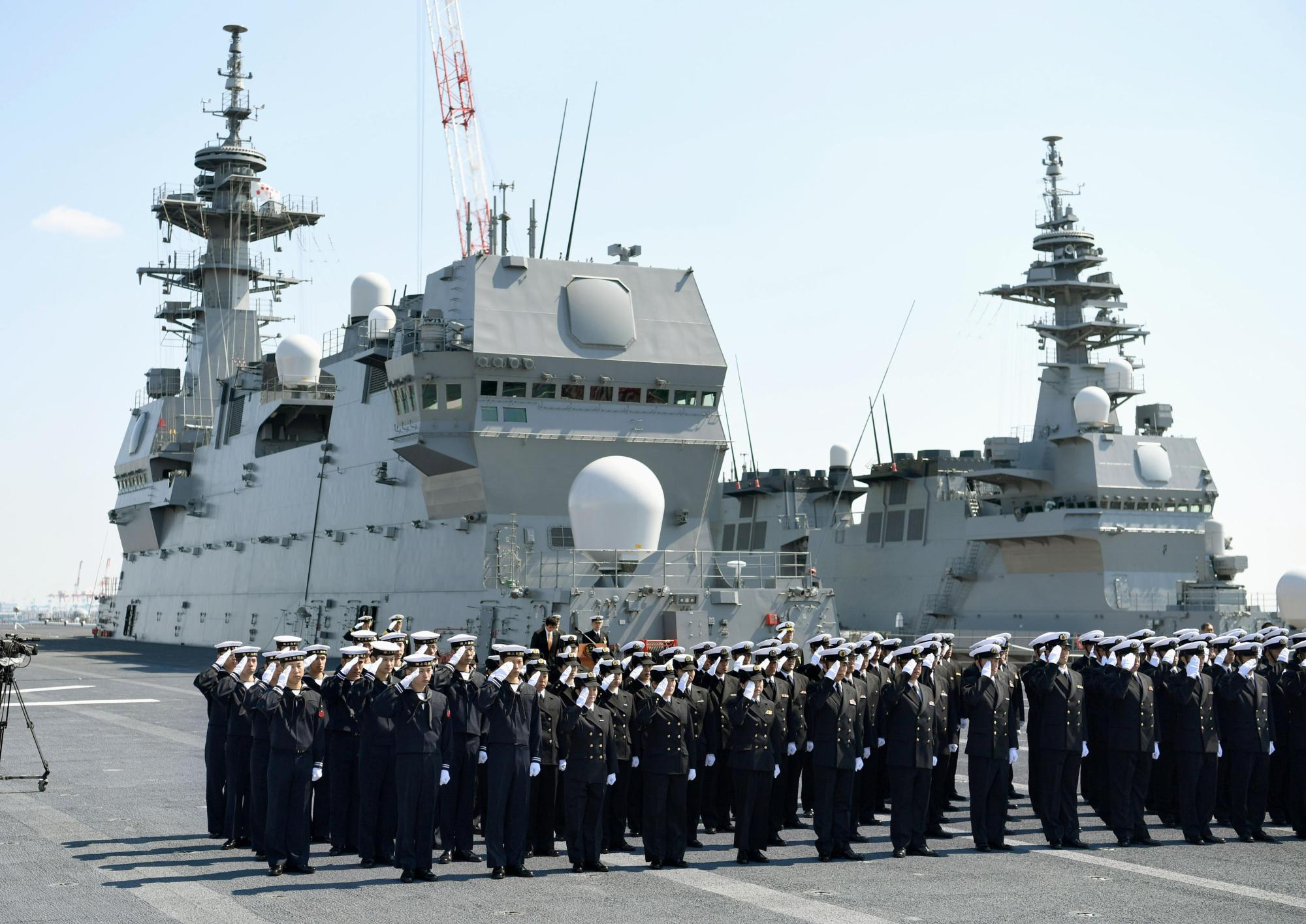 Maritime Self-Defense Force personnel salute on the flight deck of the Kaga helicopter destroyer in March last year. The Defense Ministry said Tuesday that it will dispatch three vessels, including the Kaga, to the South China Sea and Indian Ocean from Sunday through October. | KYODO