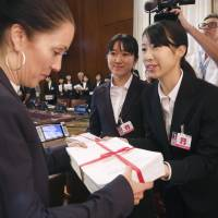 High school student peace ambassadors give signed petitions calling for the abolition of nuclear weapons to an official of the secretariat of the Conference on Disarmament on Tuesday in Geneva. | KYODO