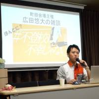 Yudai Hirota, 23, speaks about his experiences as a truant at a Futoko wa Fuko Janai (Truants Aren't Unhappy People) event in Machida, western Tokyo, on Sunday. Similar events were across the country to discuss truancy and the difficulties students face when returning to school after the summer holidays. | SAKURA MURAKAMI