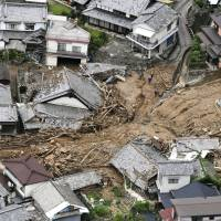 Houses damaged or wrecked by mudslides are shown in a residential area in Kure, Hiroshima Prefecture, after torrential rain inundated western Japan in July. | KYODO