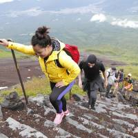 Tourists climb Mount Fuji in June 2017 after its trails were officially opened for the mountain-climbing season. | KYODO