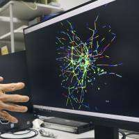In his lab at the Faculty of Science and Engineering at Chuo University in Tokyo, Azuma Taguchi, a professor of traffic networks, simulates congestion at railway stations in the metropolitan area. | KYODO