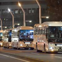 Long-distance night buses line up on a street in Tokyo's Shinjuku district in January. | KYODO