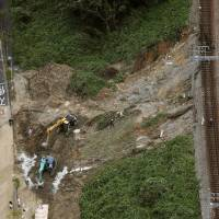 A mudslide caused by Typhoon Cimaron is seen Friday morning near train lines operated by Kobe Electric Railway Co. in Kobe, Hyogo Prefecture. | KYODO