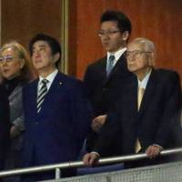 Tsuneo Watanabe (right) watches the opener for the Yomiuri Giants baseball team at Tokyo Dome along with Prime Minister Shinzo Abe on March 30. | KYODO