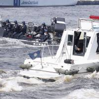 A Japan Coast Guard boat (left) confronts a suspicious vessel during a security exercise in Tokyo Bay on July 24. | KYODO