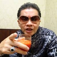 So Kuramoto, head of Takakura-gumi, scowls with a glass of tomato juice in hand at a cafe in Tokyo's Shinjuku Ward on Aug. 2. | ALEX MARTIN