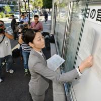 You read it here first: An employee of the National Printing Bureau in Tokyo posts pages of the Sept. 30, 2016, government gazette on its bulletin board. The pages lay out the details of two controversial security laws to expand overseas operations of the Self-Defense Forces. | KYODO