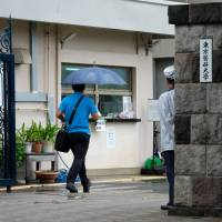A man enters the Tokyo Medical University campus on Aug. 8. The medical school has admitted that it routinely altered entrance test scores for female applicants to keep women out and apologized for the discrimination after a probe. | AFP-JIJI