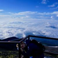 Exhaustion strikes: The author sleeps on a railing on his ascent of Mount Fuji. | OSCAR BOYD