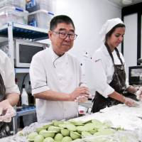 Sweet business: Takashi Ochiai rolls mochi (sticky rice cakes) with staff at his patisserie in Barcelona, Spain. | ANNETTE PACEY