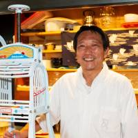 Daily grind: Himitsudo's owner, former kabuki actor Koji Morinishi, poses by his shop's hand-powered ice shaver. | WILLIAM MEERWARTH