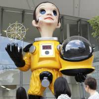 Going nuclear: Pedestrians look at 'Sun Child,' a controversial 6.2-meter statue of a child who is clad in a protective suit, in the city of Fukushima on Aug. 12. | KYODO