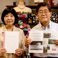 For a friend: Tomiko Kawano and Seiji Okamura of Peace Minds Hiroshima show the notebooks their group began making this year from recycled paper cranes. | PETER CHORDAS