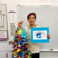 Yuya Naka, President of the Thousand Crane Club at Hiroshima International School, displays a string of 1,000 cranes sent from Primarschule Neuwies, a school in Germany. | COURTESY OF THE THOUSAND CRANE CLUB