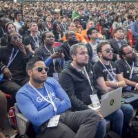 Attendees  watch a presentation at a Google conference in Mountain View, California, on May 8. Pressure from thousands of Google workers led CEO Sundar Pichai to end the firm's participation in a program to create a customized AI surveillance engine for military drones. | BLOOMBERG