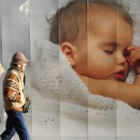 An elderly couple walk past an advertisement displaying a picture of a baby in Tokyo in December 2008. Experts say there are two ways to stabilize the Japanese population: immigration and higher fertility. | BLOOMBERG