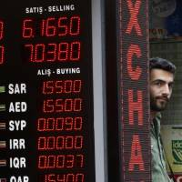 A shop owner stands next to a currency exchange shop in Istanbul on Friday as Turkey's lira fell once again amid exchanged threats with the United States. | AP
