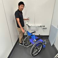 Yusuke Yamaguchi of the Paralympic Support Center demonstrates the Para Arena's barrier-free shower room, which is designed to allow access by athletes in wheelchairs. | YOSHIAKI MIURA