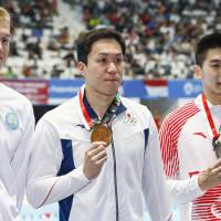Gold medalist Yasuhiro Koseki (center), silver medalist Yan Zibei (right), of China, and Kazakhstan's Dmitriy Balandin, who took bronze, pose for photos after the men's 100-meter breastroke final at the Asian Games in Jakarta on Wednesday. | KYODO