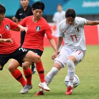 Japan's Aimi Kunikate (right) controls the ball as South Korea's Kim Hyeri (left) defends during their match at the Asian Games in Palembang, Indonesia, on Tuesday. | AFP-JIJI